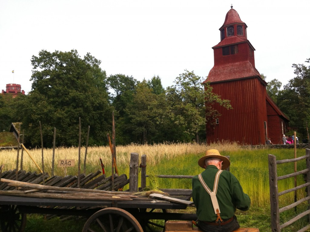 Farmer busy at his trade. The red building is Seglora Church from 1730 moved to Skansen in 1916. It's still used for weddings today!