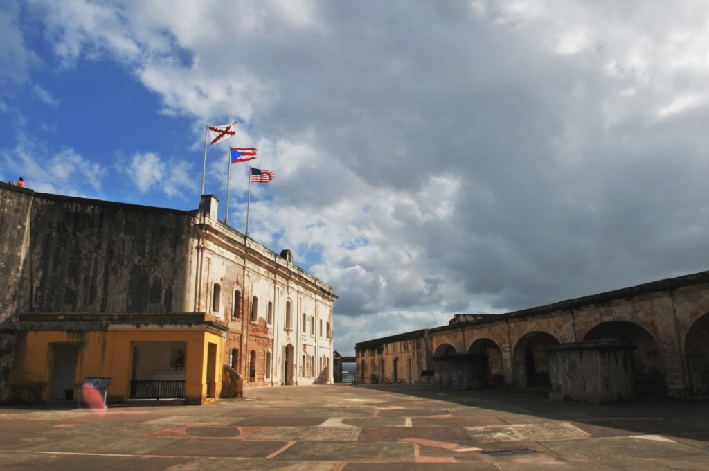 The three flags seen from the courtyard are the US flag, the Puerto Rican flag and the Cross of Burgundy, an old Spanish Military flag.